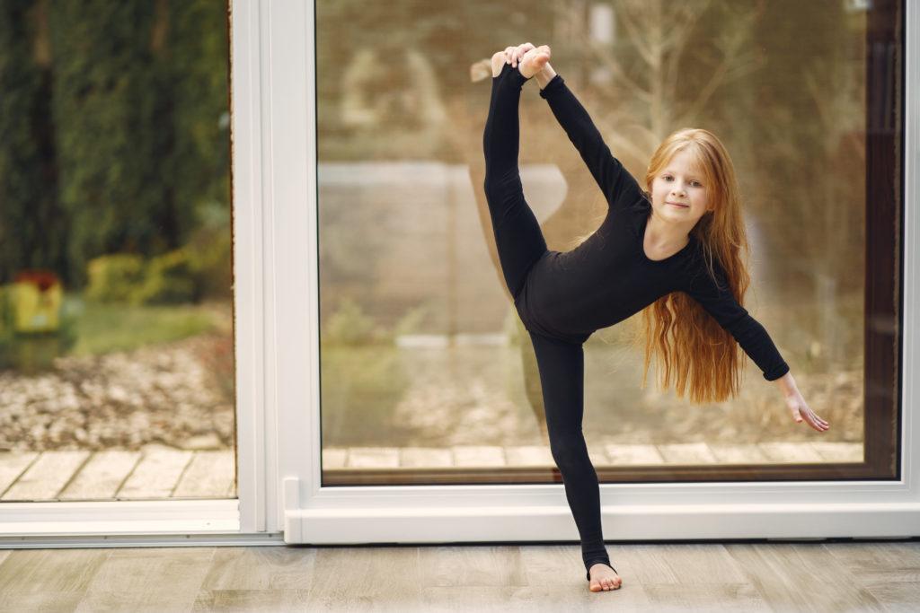 dziewczynka ćwicząca przy oknie